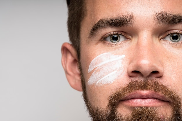 Ritratto di uomo bello utilizzando crema per il viso con copia spazio
