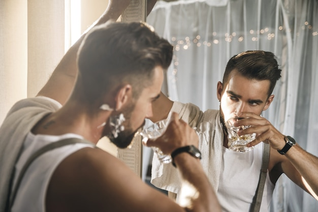 Portrait of handsome man with a glass of whiskey is looking in the mirror