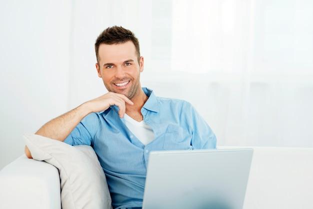 Ritratto di uomo bello con il portatile sul divano