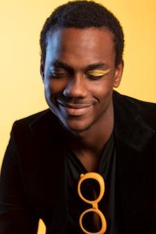 Ritratto di un bell'uomo con occhiali da sole e trucco per gli occhi su sfondo giallo