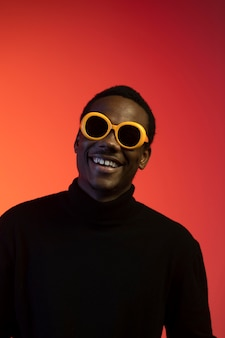 Portrait of handsome man with sunglasses over orange background