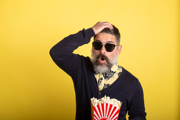 Portrait of handsome man with white beard and sunglasses looking incredulously at camera holding a box full of popcorn on yellow background.