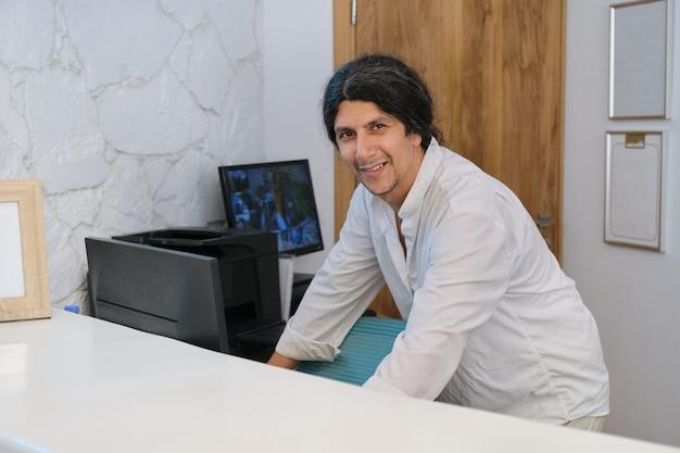 Portrait of handsome man working at the reception desk in resort hotel