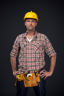 Portrait of handsome manual worker with tool belt