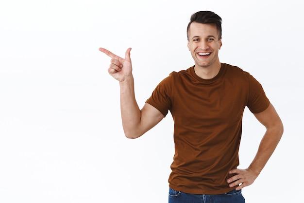 Ritratto di bel giovane maschile che punta il dito sullo spazio della copia copy