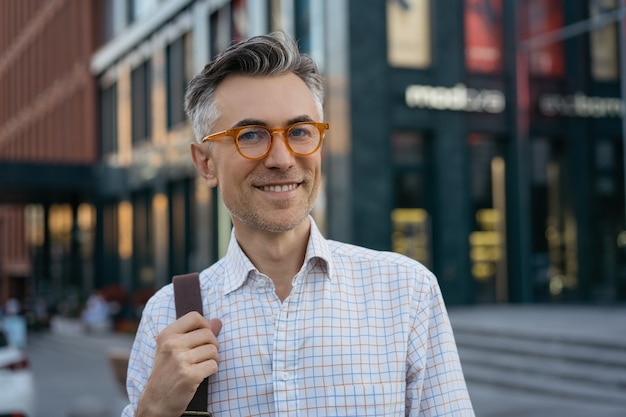 Portrait of handsome mature businessman wearing stylish eyeglasses, looking at camera, smiling