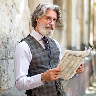 Portrait of handsome mature man reading newspaper