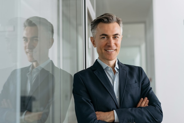 Portrait of handsome mature manager with arms crossed looking at camera, smiling standing in modern office