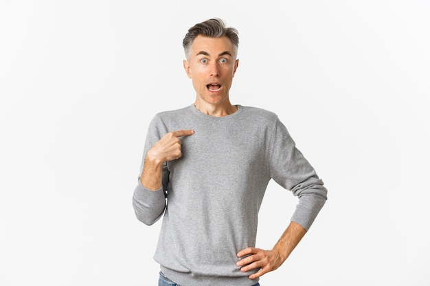Portrait of handsome middle aged gay man looking surprised, pointing at himself