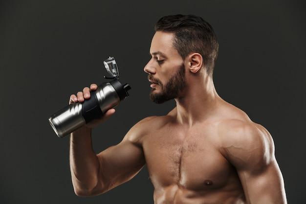 Portrait of a handsome muscular bodybuilder drinking water
