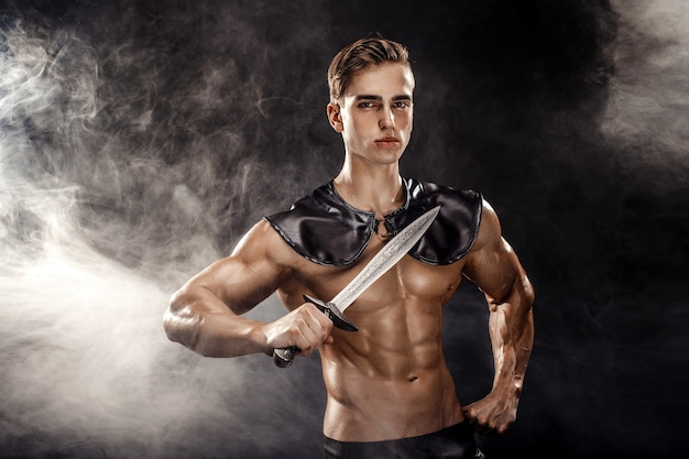 Portrait of handsome muscular gladiator with sword. isolated. studio shot
