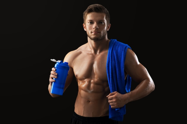 Portrait of handsome muscular man posing with  bottle of water