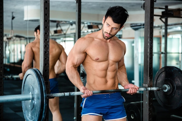 Portrait of a handsome muscular man workout with barbell in fitness gym