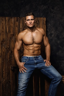 Portrait of handsome muscular and sexy man wearing jeans is posing against wooden wall