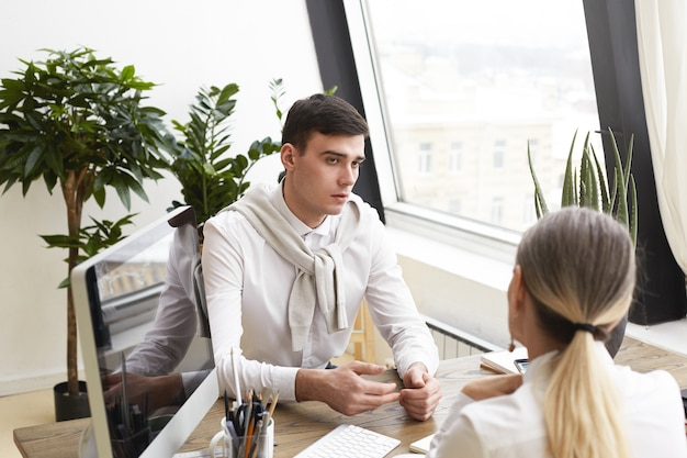 Portrait of handsome nervous young brunette male candidate answering questions of unrecognizable female human resources specialist during job interview, sitting at desk in modern office interior.