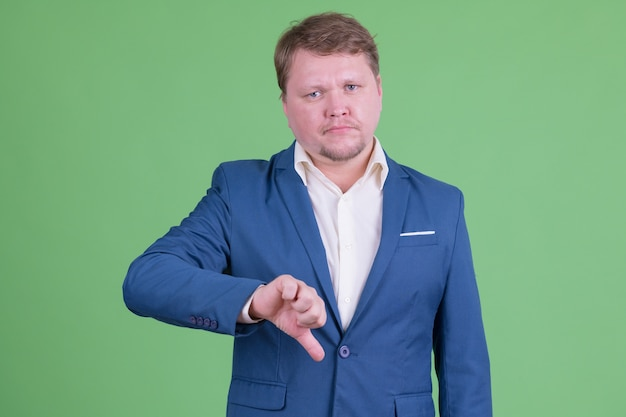 Portrait of handsome overweight bearded businessman wearing suit against chroma key or green wall