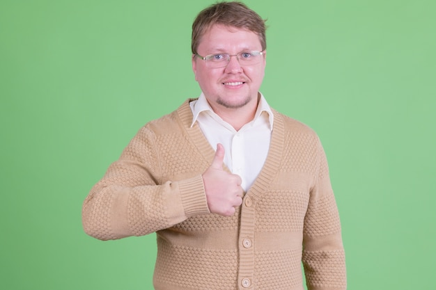 Portrait of handsome overweight bearded man with eyeglasses against chroma key or green wall