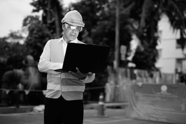 Portrait of handsome persian man construction worker at the construction site in black and white