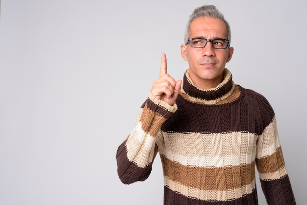 Portrait of handsome persian man thinking and pointing up ready for winter