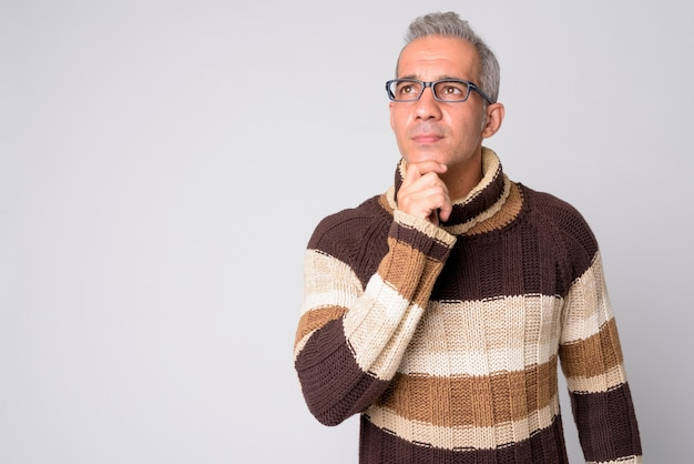 Portrait of handsome persian man thinking with eyeglasses ready for winter