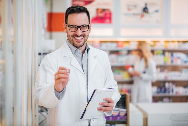 Portrait of a handsome pharmacist with clipboard, smiling at camera.