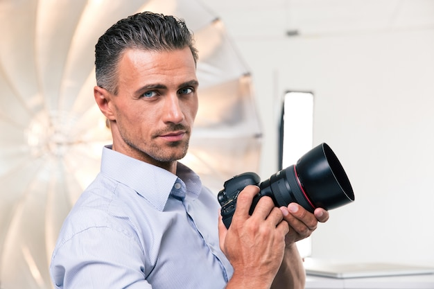 Portrait of a handsome photographer holding camera