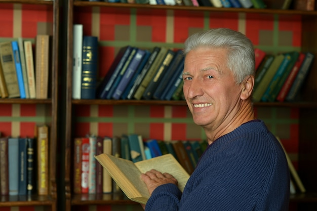 Portrait of handsome retired man reading book