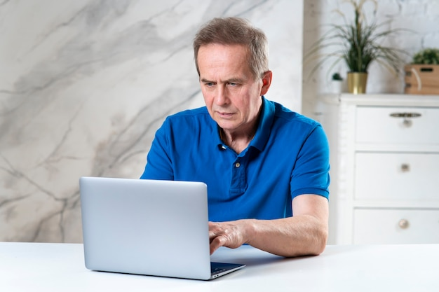 Portrait of handsome senior elderly mature concentrated man working using his laptop computer typing