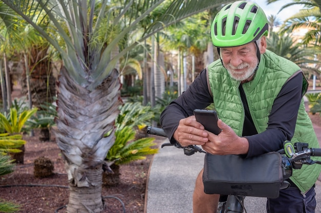 Portrait of a handsome senior man using smart phone while bike ride in outdoor tropical place. white-haired retiree enjoying his free time