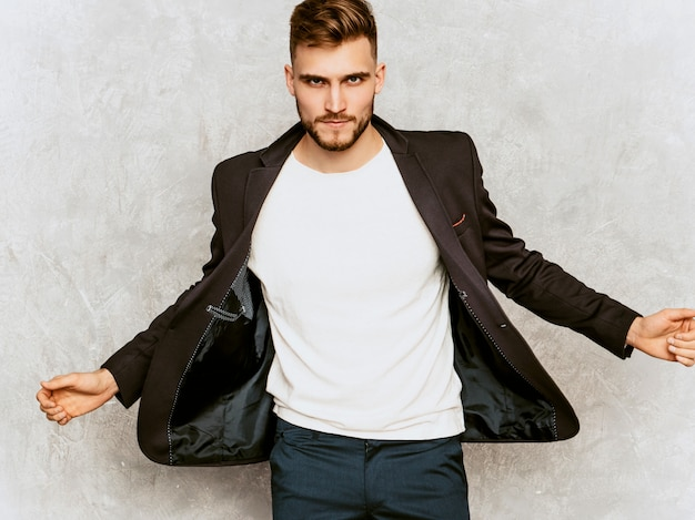 Portrait of handsome serious hipster   businessman model wearing casual black suit.