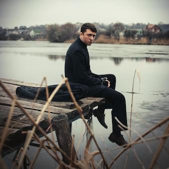 Portrait handsome serious man in coat outdoors in autumn