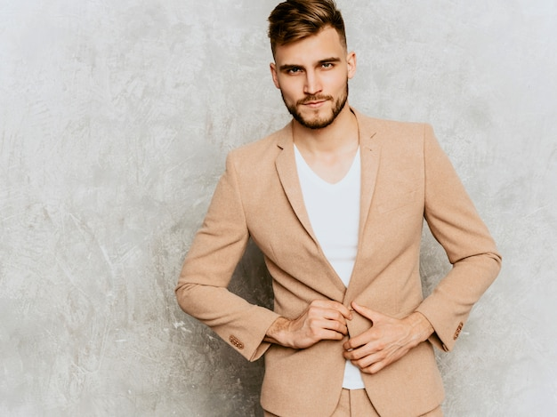 Portrait of handsome serious modern hipster   businessman model wearing casual beige suit.