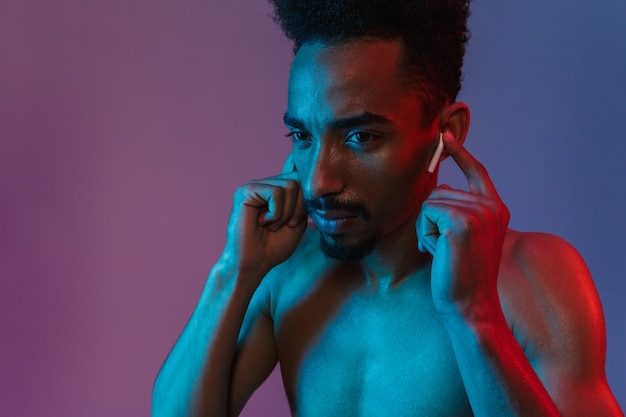 Portrait of handsome shirtless african american man posingwith earpod isolated over violet wall