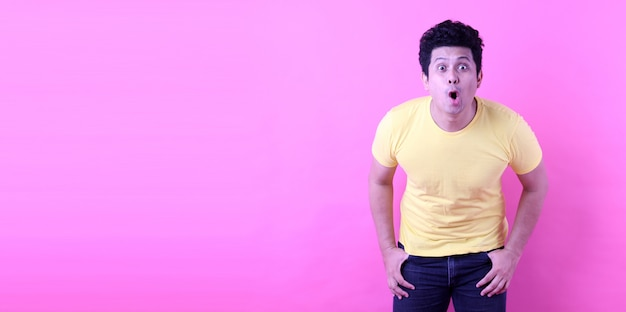 Portrait of handsome,shock and surprise face of asian man on empty space isolated on pink background in studio with copy space.