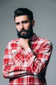 Portrait of handsome single bearded young man with serious expression over gray wall with copy space