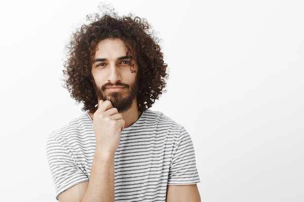Portrait of handsome smart and creative hispanic guy with afro haircut, holding hand on chin