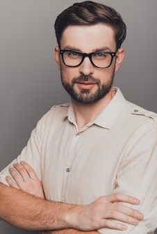 Portrait of handsome smart man in glasses with crossed hands
