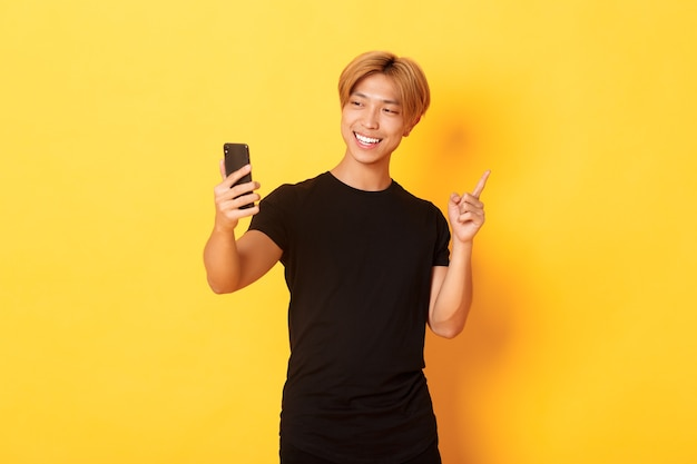 Portrait of handsome smiling asian man having video call on smartphone and pointing finger at something, standing yellow wall