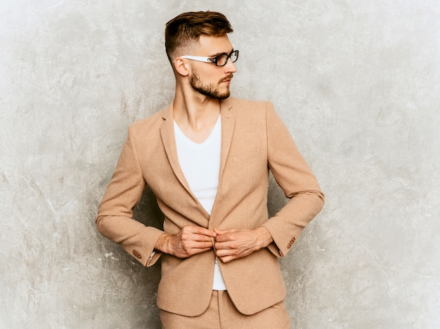 Portrait of handsome smiling hipster   businessman model wearing casual beige suit.