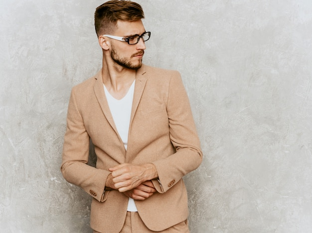 Portrait of handsome smiling hipster   businessman model wearing casual beige suit