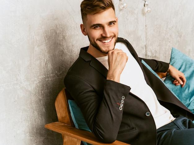Portrait of handsome smiling hipster  businessman model wearing casual black suit.