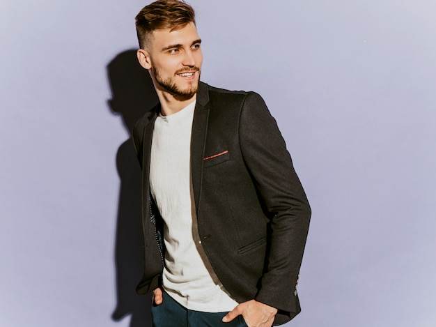 Portrait of handsome smiling hipster  businessman model wearing casual black suit.