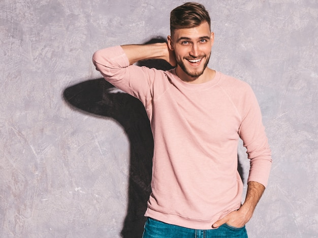Portrait of handsome smiling hipster   businessman model wearing casual summer pink clothes.