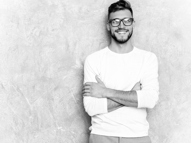 Portrait of handsome smiling hipster   businessman model wearing casual summer white clothes . crossed arms