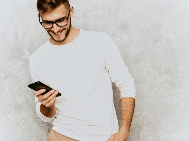 Portrait of handsome smiling hipster   businessman model wearing casual summer white clothes.. with mobile phone