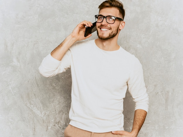 Portrait of handsome smiling hipster   businessman model wearing casual summer white clothes.