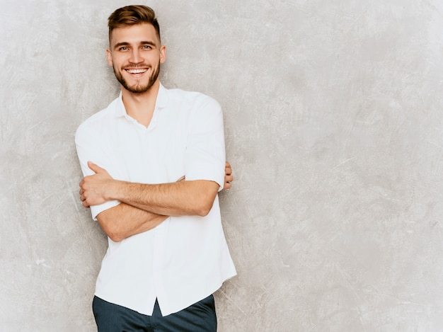 Portrait of handsome smiling hipster  businessman model wearing casual summer white shirt. .crossed arms