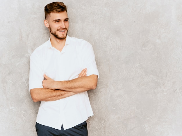 Portrait of handsome smiling hipster  businessman model wearing casual summer white shirt. . crossed arms