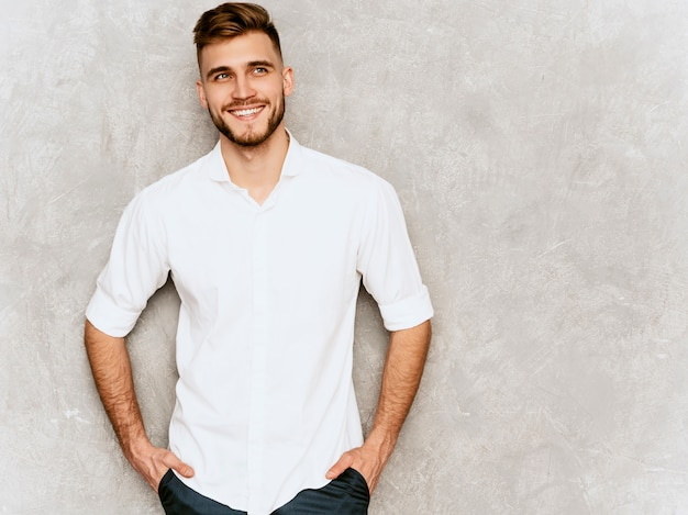 Portrait of handsome smiling hipster  businessman model wearing casual summer white shirt. . hands in pockets