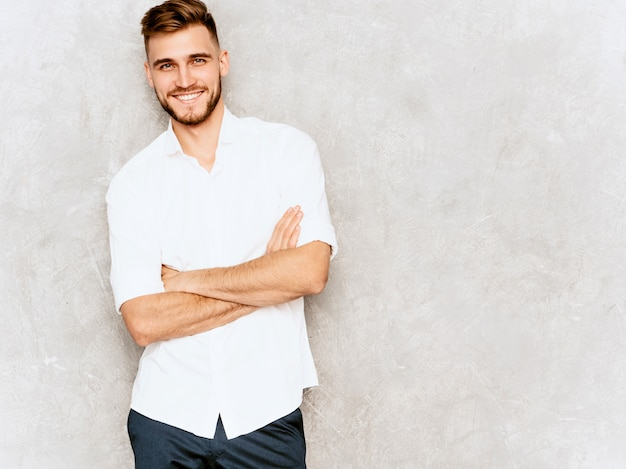 Portrait of handsome smiling hipster  businessman model wearing casual summer white shirt.